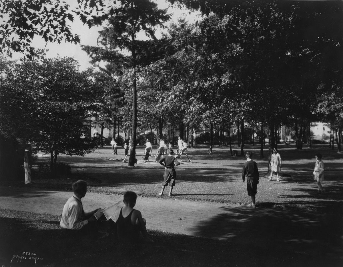 Black and white photo of school-age kids playing, standing and sitting on lawn interspersed with trees.