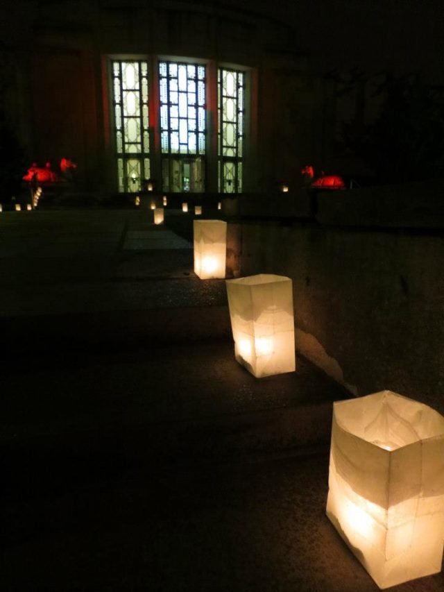 Nighttime, color photo of three luminaires (paper bags illuminated from the inside with candles) in the foreground, with illuminated glass wall in background.