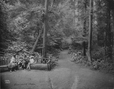 Black and white photo of woodland clearing and trail. A family of four in early 20th-century clothing sit on benches, made from hewn tree trunks with round poles for backs and rails, at the left edge of the photo.