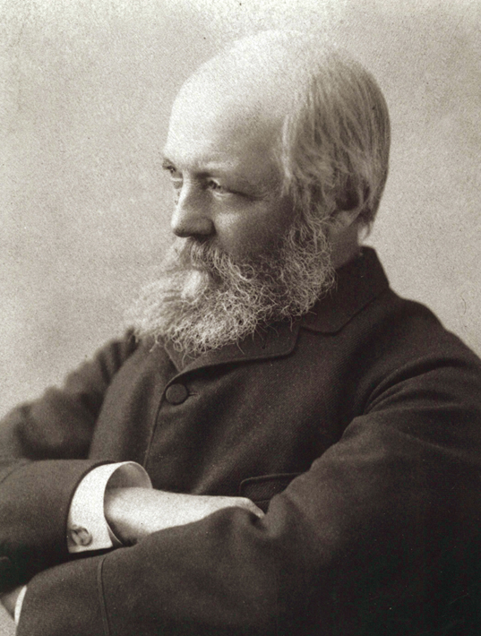 Sepia photo of balding, gray-bearded man in dark coat with arms crossed, head tilted slightly and gazing off to left of frame.
