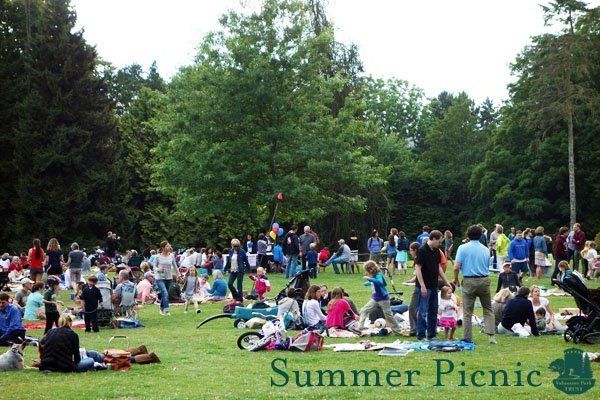 """A large crowd of people standing and sitting on blankets on a lawn. Text at bottom of photo reads """"Summer Picnic"""" and includes logo with words """"Volunteer Park Trust"""""""