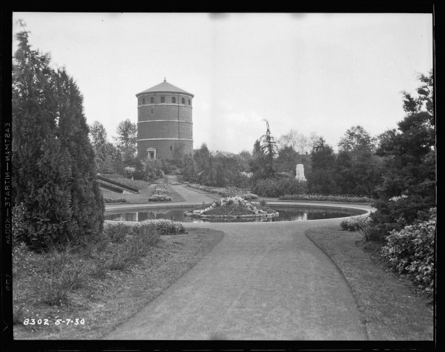 Black and white photo of groomed dirt or gravel path leading to and around circular pond with round, mounded island in middle. Path is seen continuing past pond to a circular brick tower. Surrounding vegetation includes plantbeds, young conifer trees, lawn and clipped hedge.