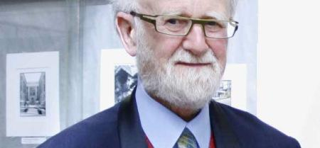 partial head and shoulders photo of white-bearded man with glasses looking at camera. Top of head is outside frame.