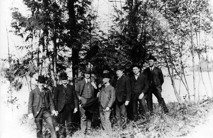 Black and white photo from 1903 showing eight men standing on grassy slope with copse of trees behind them.