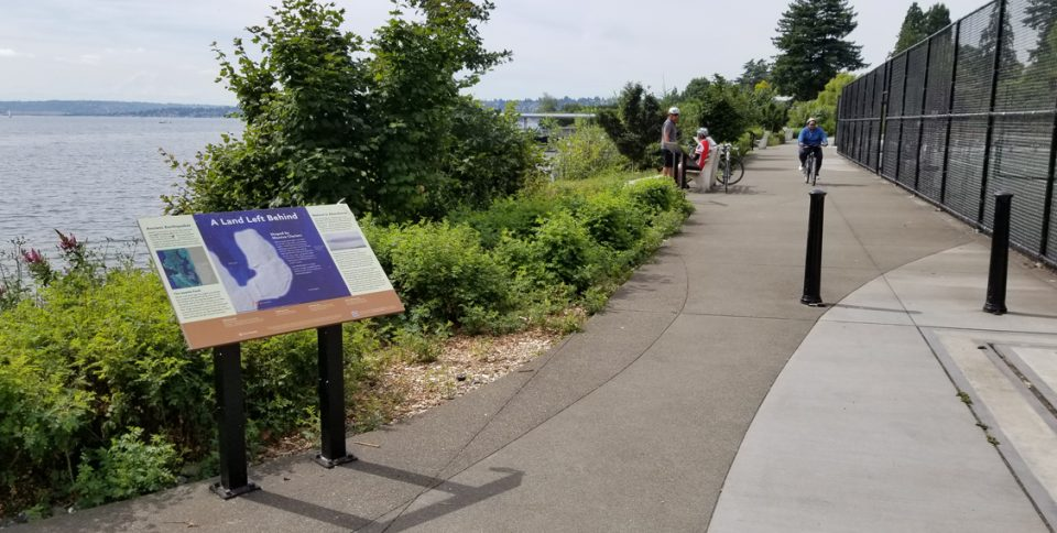 photo of interpretive panel and paved path beside tennis courts and along shoreline